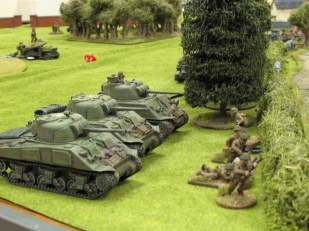 Sherman tanks supporting an infantry unit while support weapons move up in the background