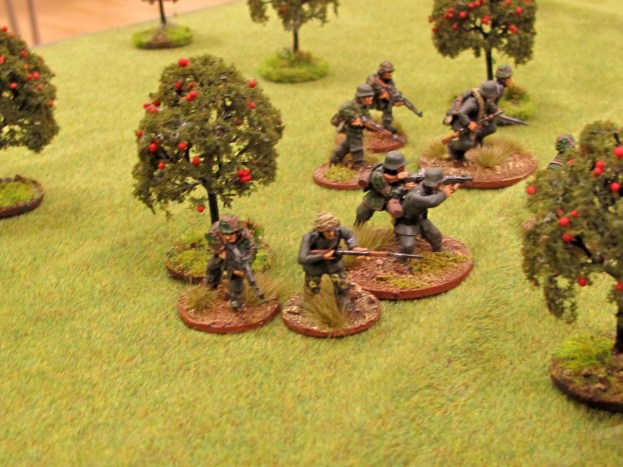 The lead German squad moves up through the orchard