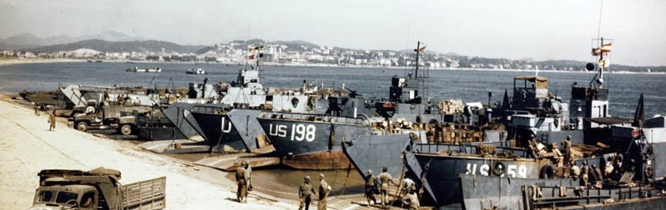 A row of grey landing craft pulled up onto a sandy beach
