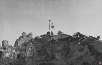 A Polish flag is raised by two men standing on the ruins of the abbey