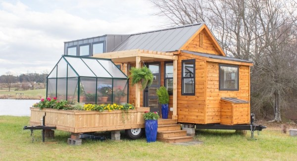 Tiny home on wheels with adjoining patio and green house for Tiny house zillow