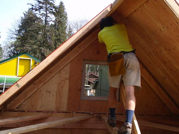 Travis Roofing his Prefab Tiny Cabin