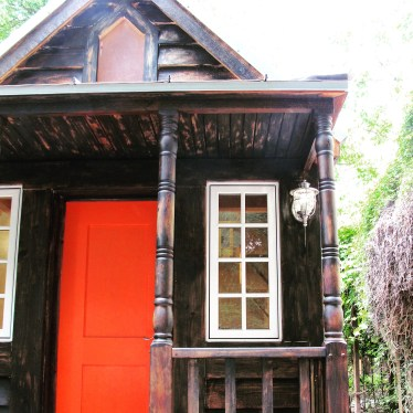 The front porch. Orange-tomato red door. Stone white windows.