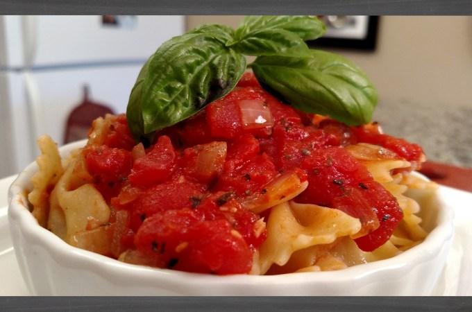 Tomato Sauce on farfalle pasta in white dish with basil