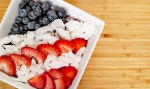 Red white blue acai bowl. blueberries, sliced strawberries, coconut flakes in white bowl on bamboo cutting board