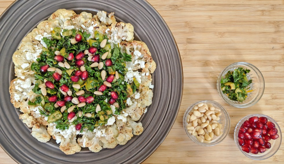 Roasted Cauliflower with Parsley, pomegranate seeds, olives, mint and feta cheese on a brown plate