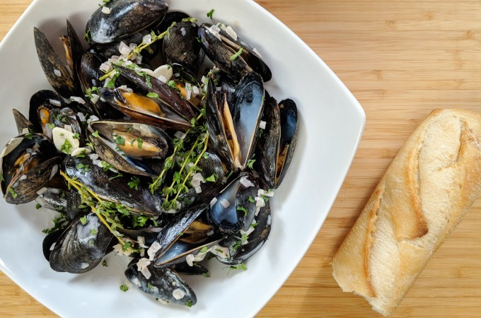 A bowl of blue/black mussels with a crusty baguette. Classic French mussel recipe with Garlic, shallots and thyme flavor the dish.