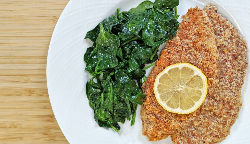 Tiny Kitchen Keto Almond Crusted Fish with lemon and wilted spinach on white plate and bamboo cutting board