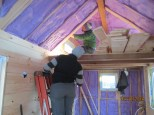 Stefan getting the top piece of siding in on the dormer.