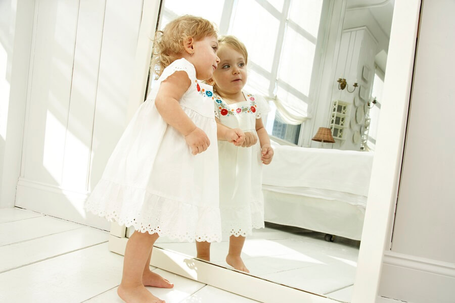 baby girl looking into the mirror