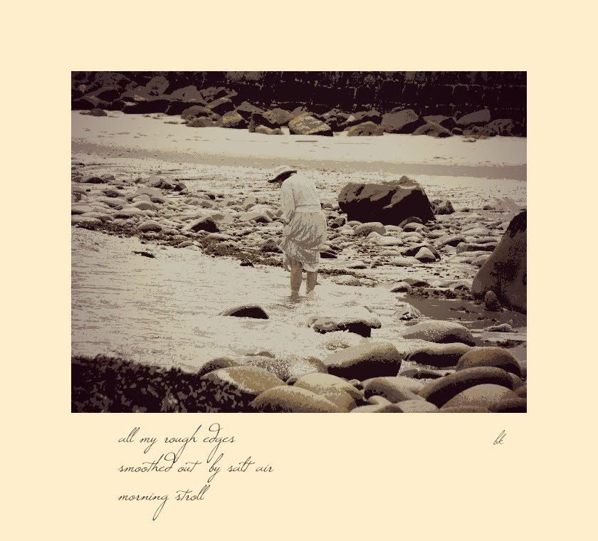 Monochrome photo of a woman wading at the seashore, with script text of a haiku below