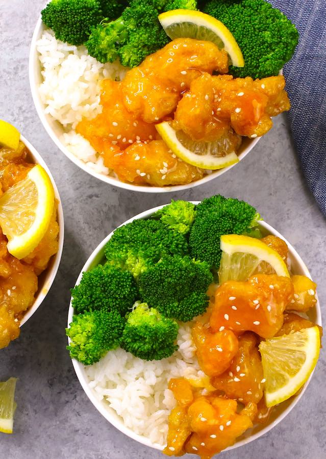 Chinese Lemon Chicken served in rice bowls with broccoli and garnished with sesame seeds and lemon wedges