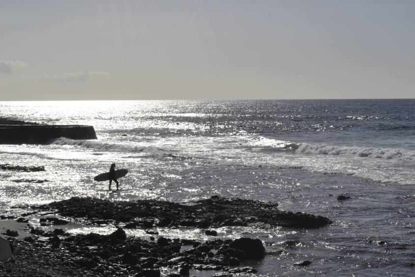 Surfer nell'oceano alla spiaggia Playa las Americas a Tenerife