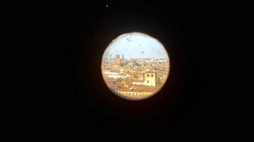 """Vista su Bologna """"La Rossa"""" da una fessura nel muro durante la salita al Campanile di San Pietro"""