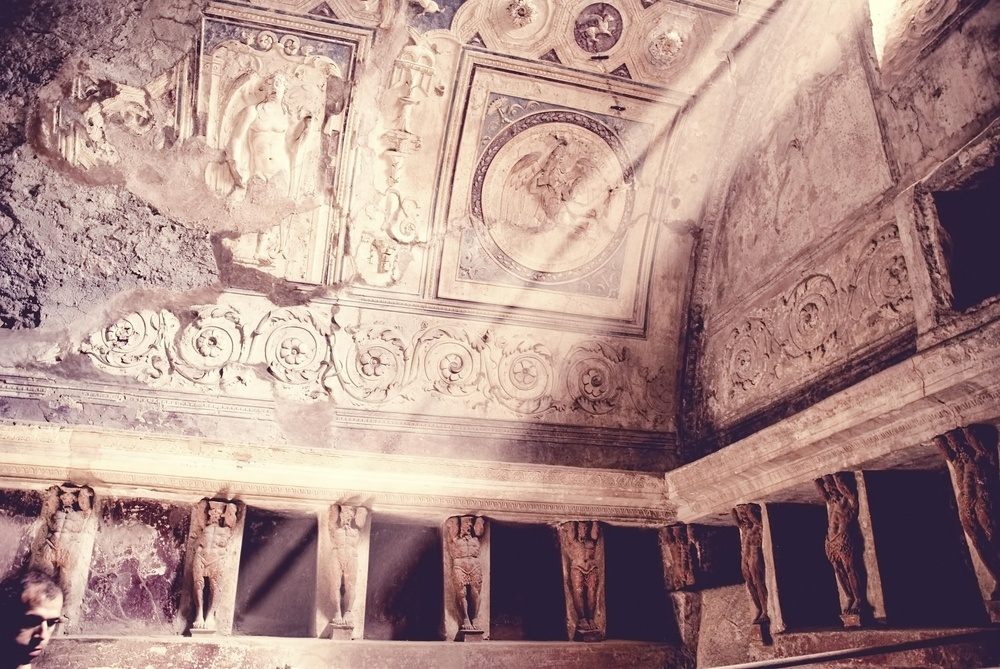 Light pours into the public baths of Pompeii and illuminates the statued walls.