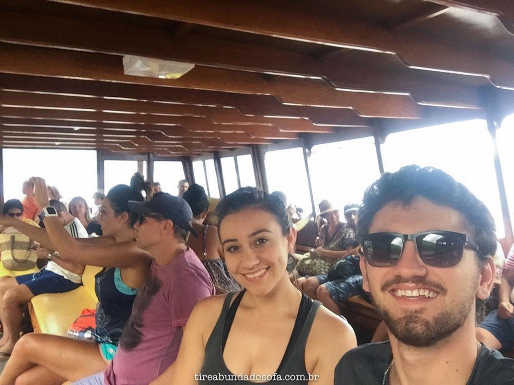 casal andando com o barco da costa da lagoa, em florniaópolis