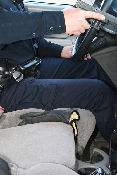 La pistola se lleva a la posición de las tres al lado del volante mientras la mano de apoyo suelta el cinturón y agarra la maneta para abrir la puerta.