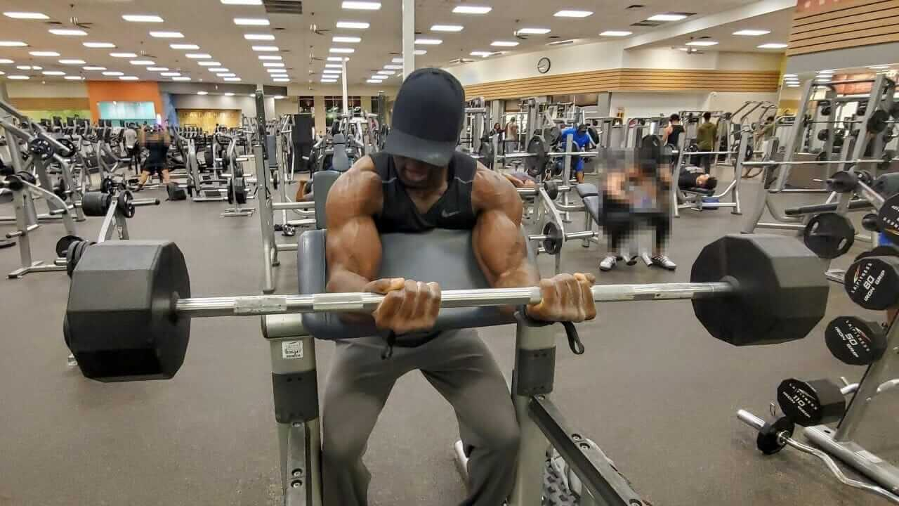 Nurudeen Tijani working out biceps doing barbell preacher curls in gym