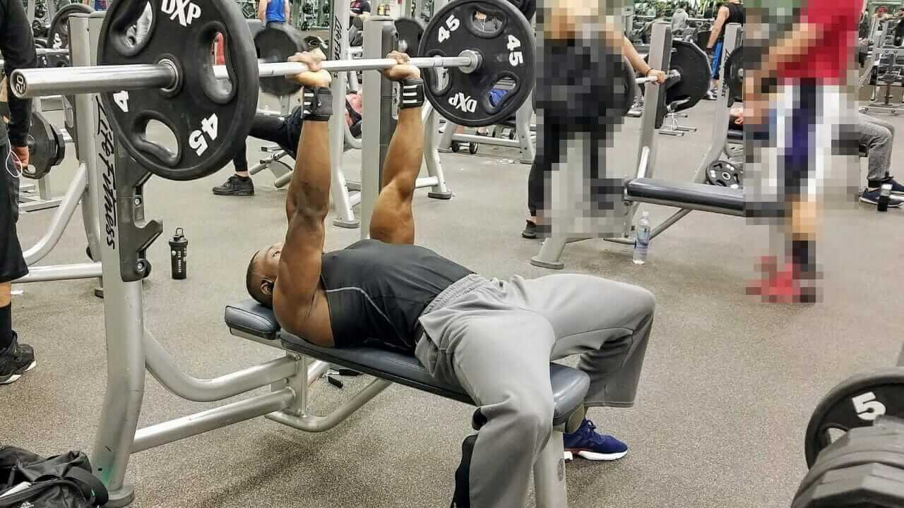 Nurudeen Tijani working out triceps doing close-grip bench press in gym