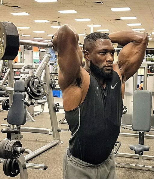 Nurudeen tijani doing overhead triceps extensions with a barbell at gym