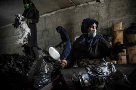 """Gorgan, Iran – Jun 2020. Zahra, 37, is a daily-paid worker at a charcoal packaging workshop. She, who is a mother of one, has been working there for almost three years. """"The workshop had been closed due to coronavirus outbreak, but three days after its closure I asked our employer to let us return to work and he accepted, however, if he did not do so, I might have to beg for food since my husband had become unemployed as well and made no money already for two months,"""" she said. """"It is indeed a truly laborious work that I do illegally these days. Nevertheless, to choose between the bad and the worse we have no option but to opt for the bad,"""" she added. This manual charcoal packaging workshop that employs ten workers, six of whom are women, has been in business for four years. The workshop had been closed as many other businesses had due to coronavirus outbreak. """"After the workshop had been closed for three days, the employees were continually calling and asking to return to work; thereafter, we started working again at the request of the employees,"""" the workshop manager said. ( Photo Credit: Hamed Barchian/ NVP Images)"""