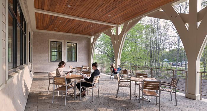 A photo of the library's patio with several sets of tables and chairs with three women sitting and reading at them