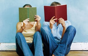 Two people sitting on the ground holding open books in front of their faces