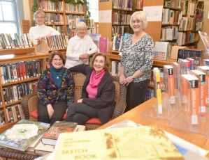 A photo of five elderly women with sitting on a couch and three standing behind it in between bookshelves