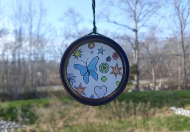 suncatcher craft take home kit hanging in the windows picture of butterflies in the center of the catcher