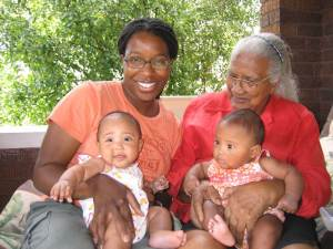 Tiya with twin daughters on her lap sitting next to her grandmother