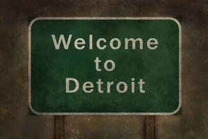welcome to detroit with a green street sign background