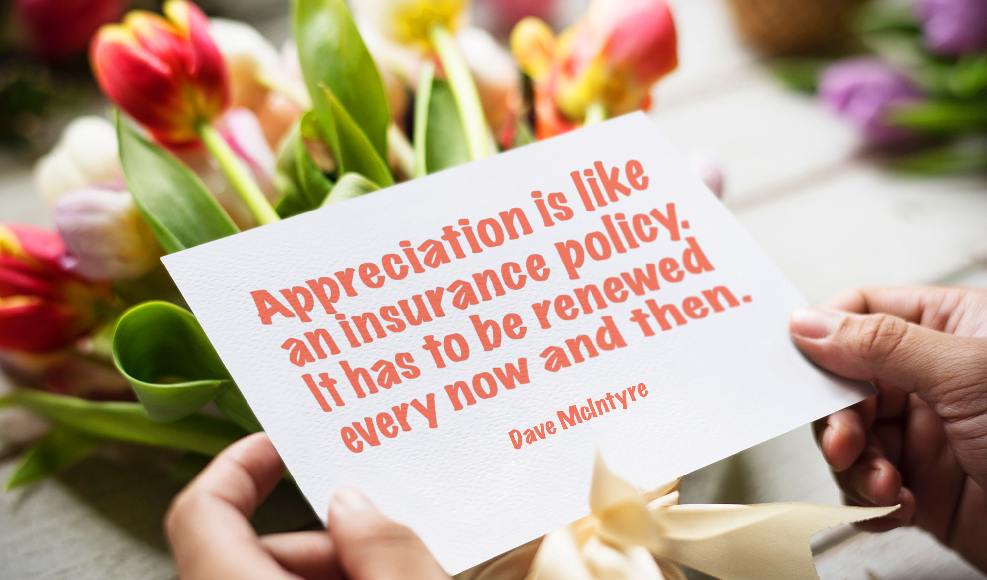 daily inspirational quote image: a bunch of flowers in the background, and a card with the daily quote in the foreground