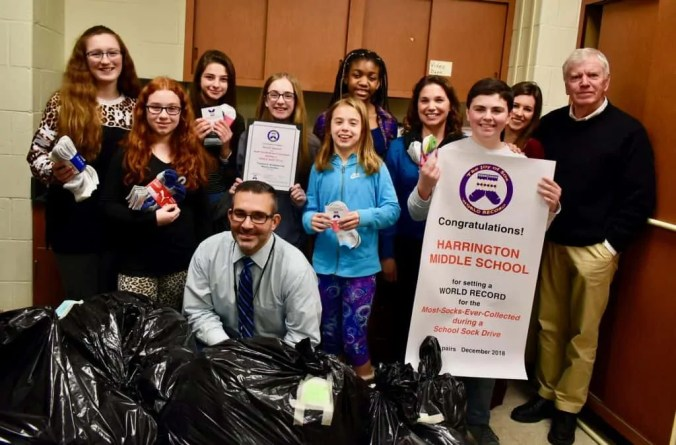 "Student Council Members from Thomas E. Harrington Middle School, Mt. Laurel NJ, collected new socks for the homeless and set a Joy of Sox WORLD RECORD for the most pairs ever collected during a K-8 school sock drive. Pictured with the students is Principal Ryan ""Mr. C"" Caltabiano, kneeling in front; teacher Kate Mitchell, fourth from right; teacher Tracy Burleson, second from right; Tom Costello, Jr. Chief Sock Person and Founder of The Joy of Sox, on the right."