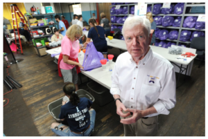 Tom Costello Jr, Chief Sock Person, as his business card says, in The Joy of Sox's warehouse. In the background are volunteers from Villanova University sorting and bagging new socks for distribution to shelters and facilities for those experiencing homelessness. Photo credit: Bradley C. Bower