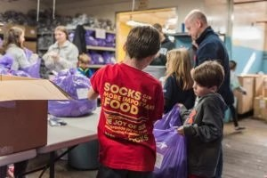 Two younger sock angles help sort and bag new socks for the homeless at The Joy of Sox's warehouse in Phoenixville, PA.