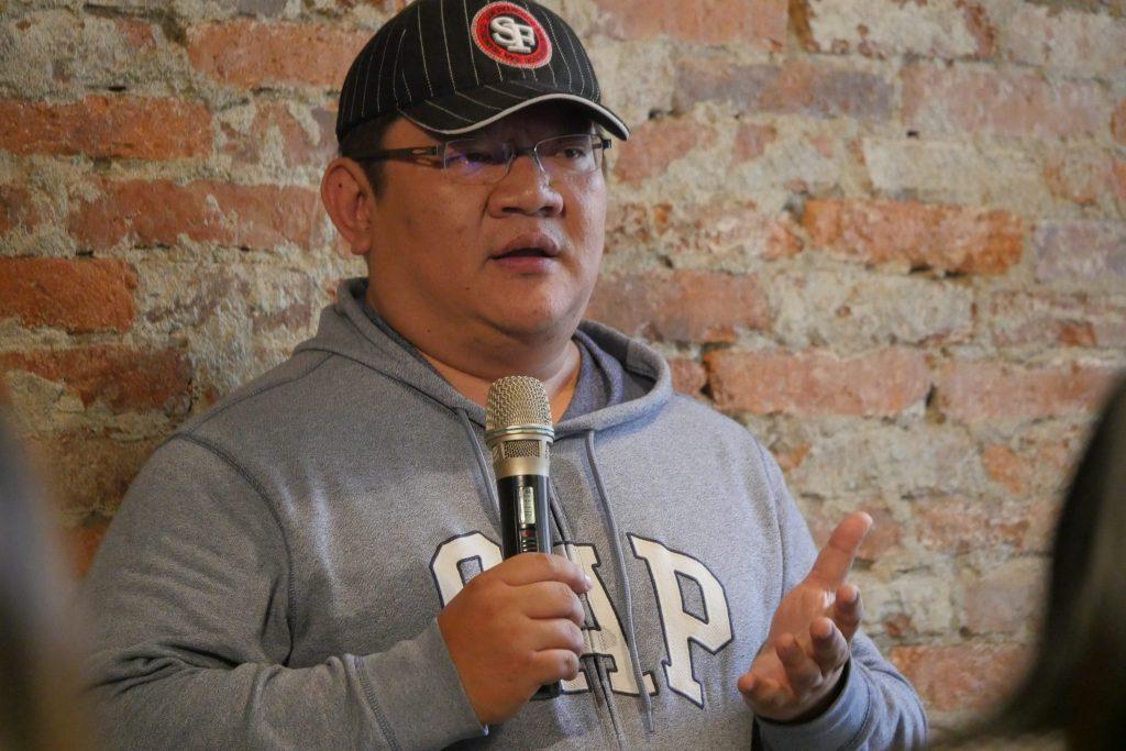 李火增的孫子-李政達先生,戴著黑色帽子,穿著灰色GAP帽踢上衣,手上拿著黑色麥克風