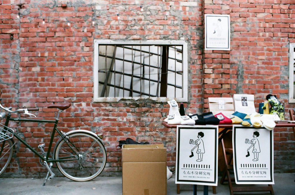 紅磚牆、一台黑色的腳踏車,有一個鐵窗,還有一個紙箱,旁邊擺著桌子上頭放著襪子