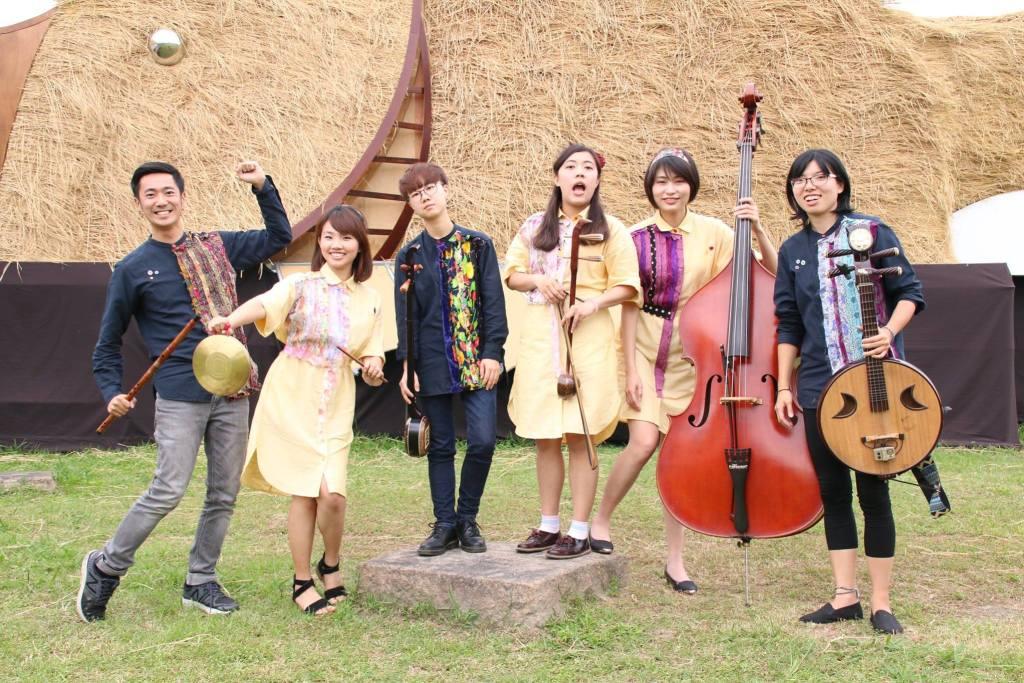 有五個人站在草皮上,穿著黑色、黃色的衣服,有人拿著大提琴、月琴、蕭等等各式各樣不同的樂器