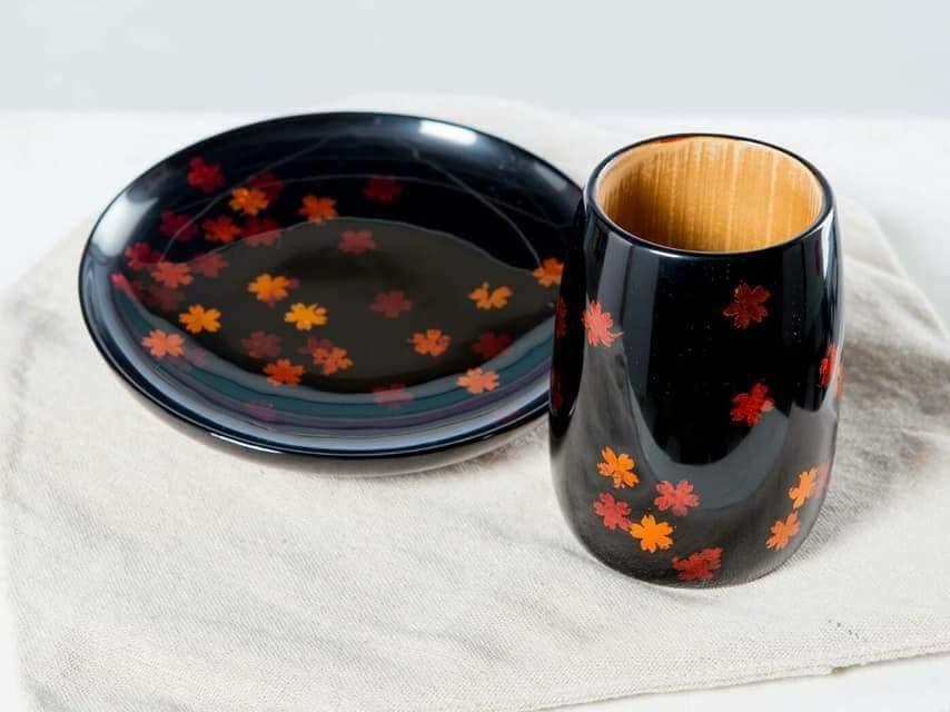 白色布上放著一個黑色盤子一個黑色杯子,上頭都有橘色的櫻花裝飾