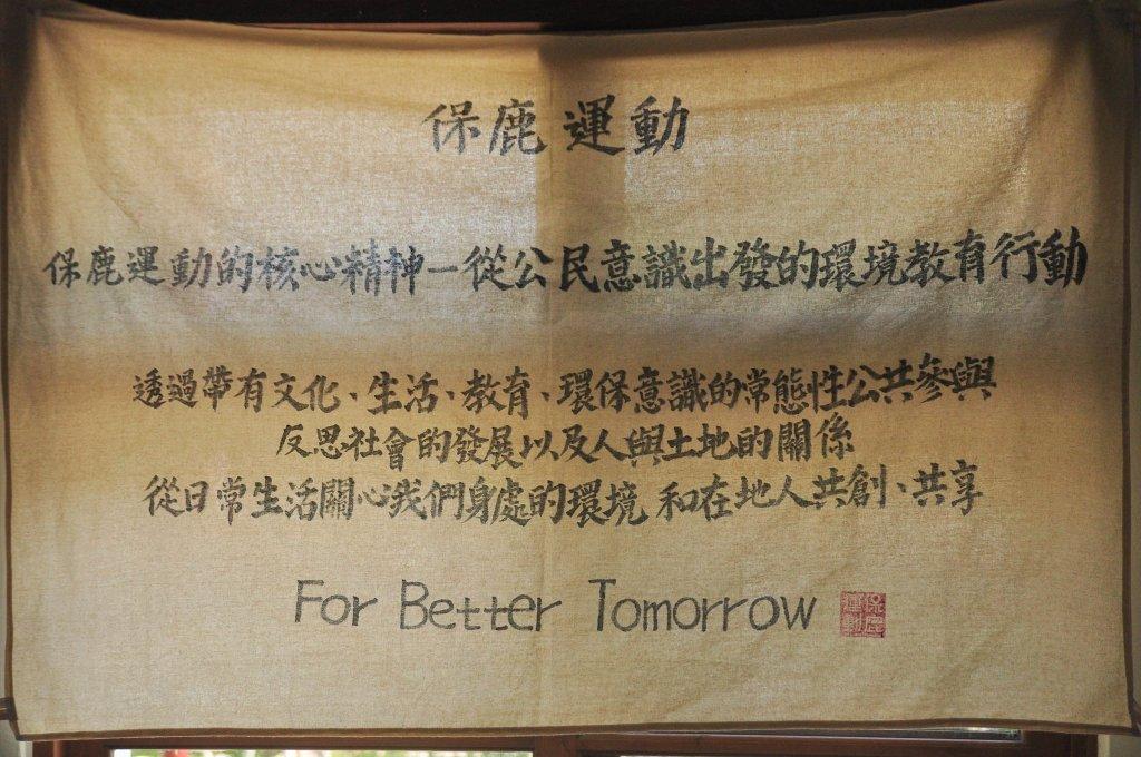 一塊米白色的布吊在窗戶上,有光透出,布上頭字用書法字體寫出