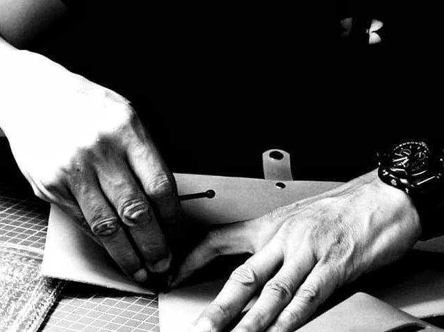 黑白照片,有一雙手帶著手錶放在桌上