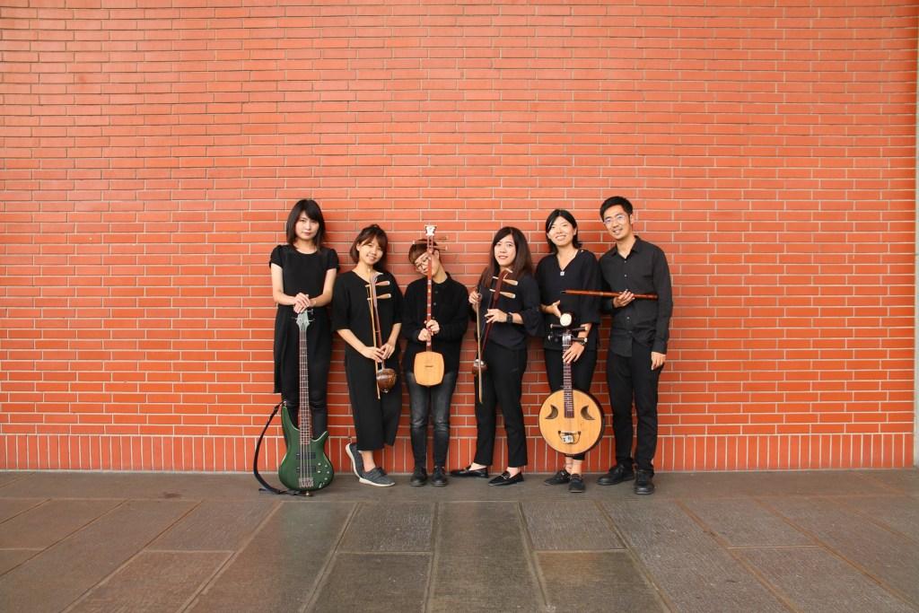 有六個穿黑衣黑褲的人站在紅磚牆前,每個人都拿著不同的樂器