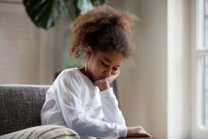 little girl sitting on the couch sad