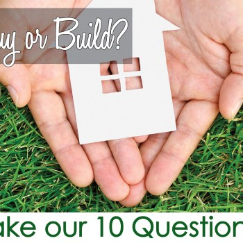 Grass background, hand holding paper cut out of a home, Buy or Build