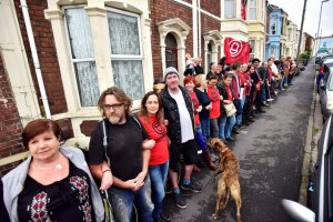 This is the moment kindhearted neighbours in Easton, Bristol, formed a human chain around a mum's house - to stop her being kicked out in a 'revenge eviction'. See SWNS story SWSAVE; Nimo Abdullahi, 39, was told she and her family would be thrown out of their home of 12 years after she complained to her landlord about damp. But in a bid to protect the mum-of-five from a 'revenge eviction', residents and campaigners turned out to stop it happening. Around 30 people stood side by side, arms linked, to build a wall of bodies in front of the privately-rented property in Easton, Bristol. All morning, more neighbours joined the blockade - with a newlywed couple living opposite the family cutting up their wedding cake to keep the protesters sustained. When bailiffs turned up at 11am on Tuesday, they weren't able to get inside.