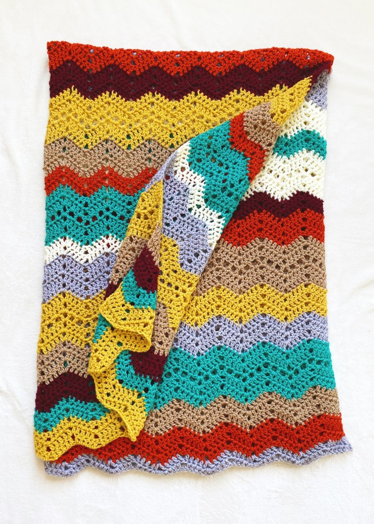 Free Crochet Blanket Pattern - Autumn Skies Afghan. Colorful crochet afghan made with worsted weight acrylic yarn in seven colors. Lion Brand Basic Stitch Premium. Easy crochet throw blanket pattern for beginners. Free pattern. | TLYCBlog.com