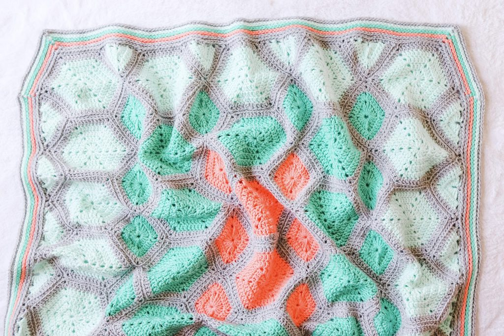 Learn to crochet a hexagon baby blanket. Free crochet pattern Hexis In Springtime from TL Yarn Crafts. Easy hexagon blanket pattern with border. How to crochet a hexagon. | TLYCBlog.com