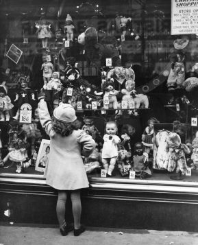 21st December 1937: A young girl points at the doll she wants for Christmas, in the window of a toy shop. (Photo by Fox Photos/Getty Images)