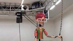 In dit werk van kunstenaar Jordan Wolfson (US) zitten allerlei rigging oplossingen verwerkt. De krachten die vrij komen wanneer deze pop door de ruimte geslingerd wordt zijn enorm. Daarom staat veiligheid en deskundig gebruik voorop. Klik op de afbeelding voor een korte impressie.