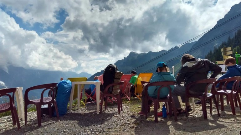 Hikers sitting in chairs and enjoying the views outside Refuge de la Flegere